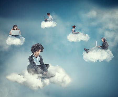 Teenagers using their laptops on different clouds suggesting a network. Stock Photo