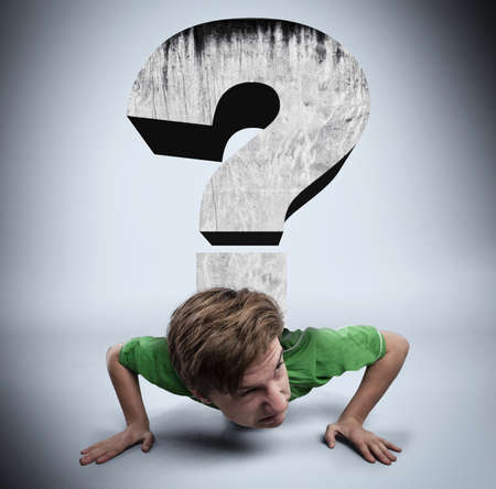 Young man is pushed by a question mark to ground. Stock Photo
