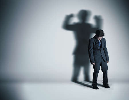 Image of a weak businessman standing depressed in front of a wall and his shadow shows streght.