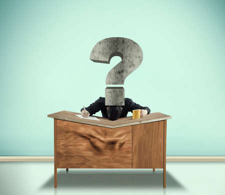 A man has  his head pushed by a question mark onto his desk and the desk had bent in the middle. Zdjęcie Seryjne