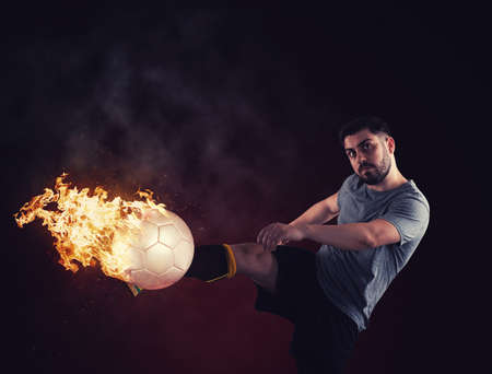 Soccer player shooting a ball in flames.