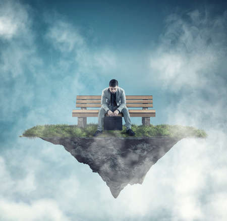 Business man sitting on the bench on a piece of land floating in the air. Stock Photo