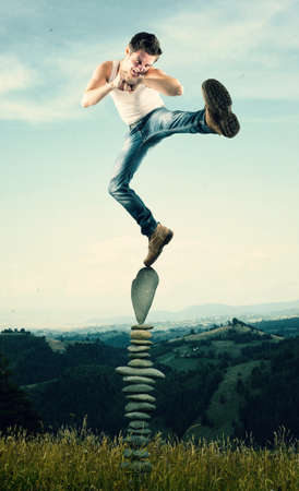 Man kicks and standing in balance on arranged rocks. Stock Photo