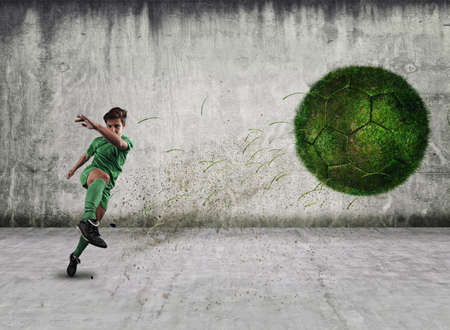 Soccer pckgrlayer shooting a ball of grass, in a urban background.