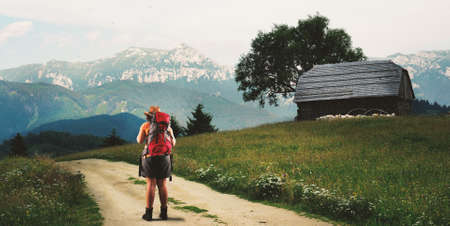 ongoing: Young girl on a road to a mountain. Stock Photo