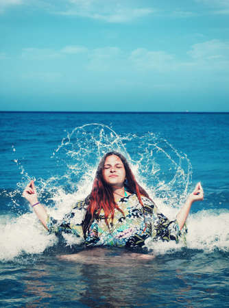 Young woman sits in a lotus position in the sea and meditates. Getting hit by a wave.