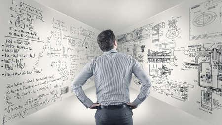 Bedrijfsmens die zich in een ruimte bevinden en wiskundeformules bestuderen die op muren worden geschreven. Stockfoto