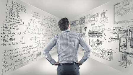 Business man standing in a room and studying math formulas written on walls.