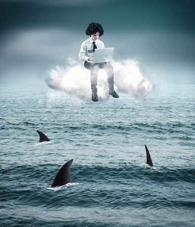Business man sitting on cloud and working on laptop adove sharks in the ocean.