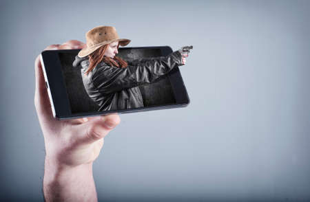 entertaiment: Hand holding a smartphone which displays a movie on touch screen.Cowboy girl gun shoot and get out of the screen.