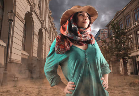 Explorer woman discovers unpopulated city . Beautiful woman wearing a cowboy hat and walking in a city covered by sand.