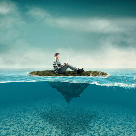 Zaken man werk op laptop zittend op een stuk land zwevend in de oceaan. Gespleten half water zeegezicht.