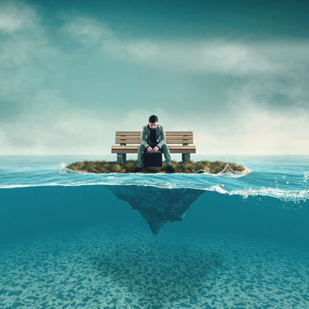 Thoughtful business man sitting on the bench on a piece of land in the ocean.  Split half-water seascape.