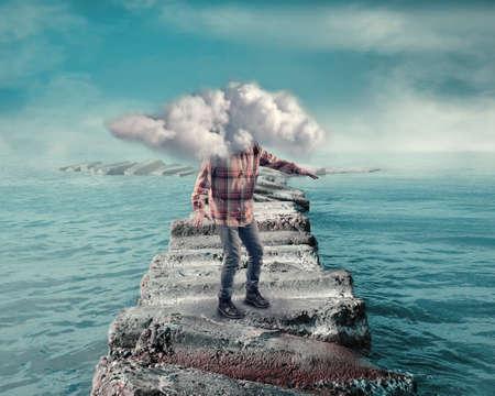 Giovane uomo coperto da una nuvola che cammina su un pontone di rocce nell'oceano.