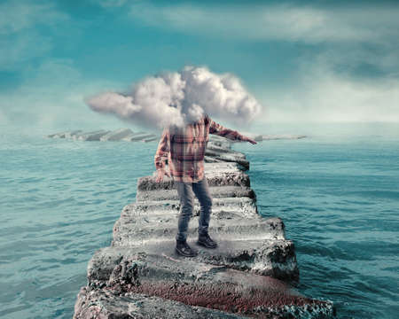 Young man covered by a cloud walking on a pontoon of rocks in the ocean. 免版税图像 - 89814190