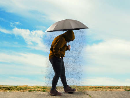 Woman holding an umbrella and raining on a sunny day. Concept of depression. Stock Photo