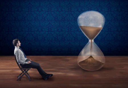 Businessman sitting on a chair and watching time passing by into a hourglass. The concept of waiting patient.