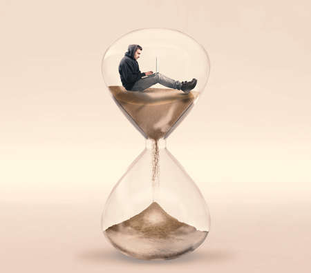 Young man working on his laptop inside of a hourglass. The concept of working with a deadline. Stock Photo