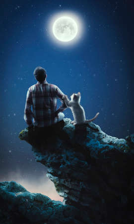 Man and his cat admires the moon on top of a cliff.
