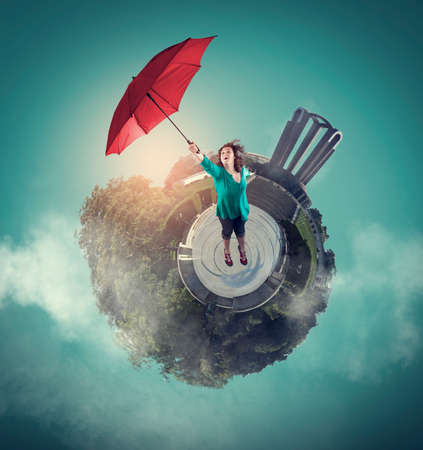 Woman getting off the ground with an umbrella. 360 degree view globe Фото со стока