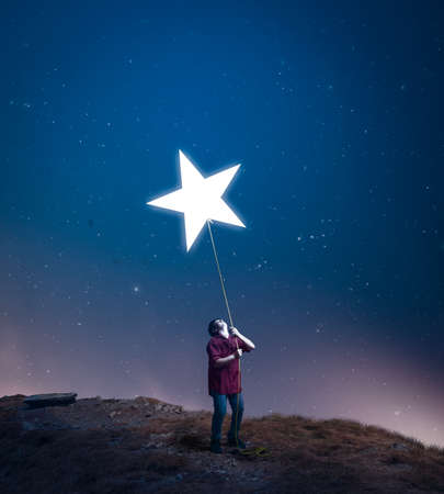 kid drag a star towards him with a rope in the middle of the night. The concept of accomplish his dreams.