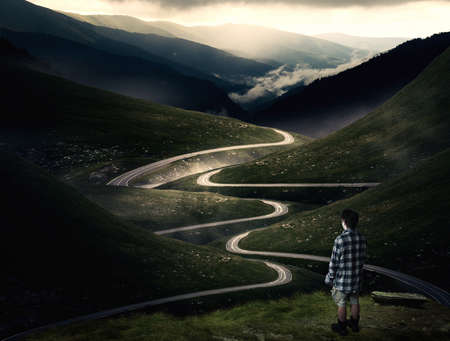 Man standing on a mountain peak admiring the view of a curved road crossing the mountains. 版權商用圖片