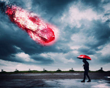 Man with an umbrella walking while a meteor is falling.