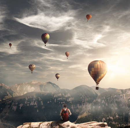 Hiker on top of a mountain peak admiring the hot air balloons flying.Enjoy the moment.