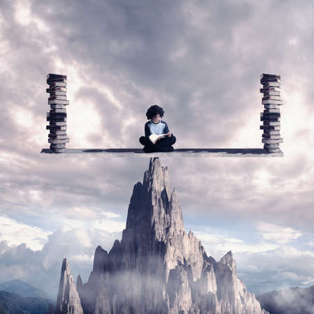 Stundent reading a book on balance scale above a mountain rock. Knowledge is power concept. Stockfoto