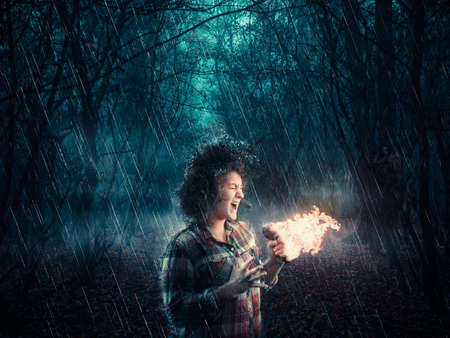 Woman in the woods sings on microphone and makes it burns while raining. Stock fotó