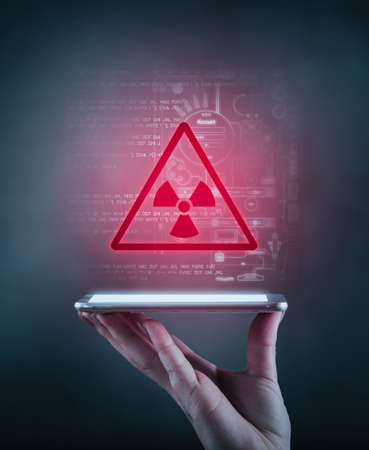 Hand holding a phone with an warning alert icon and data information in the background.The concept of threat of personal information.