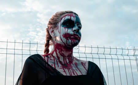 Portrait of a gothic girl wearing a black dress and a bloody make up.Halloween theme. Imagens