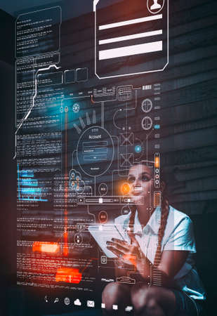 Young woman using tablet and analyze infograph tab screen with codes and information at home.Futuristic user interface. Stock Photo