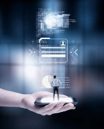 Hand holding a smartphone with businessman standing and analyze a digital screen with of codes and infographics.
