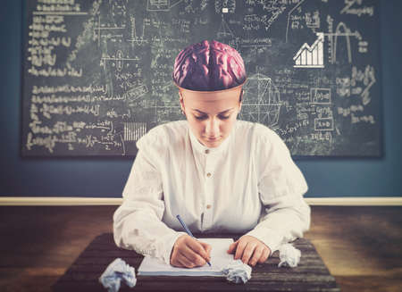 Young woman solving a math problem in a classroom with her brain out of head. The concept of setting your mind on something.