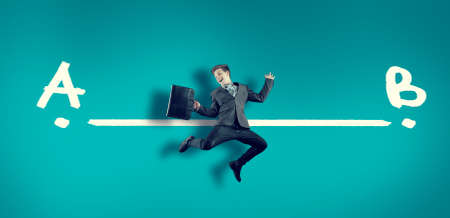Business man on a simple background jumping in front of line between from  A and point B . Stock Photo