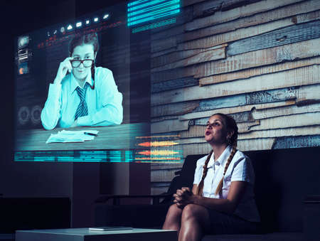 Young woman having a video call with his partner on a hologram in living room. Live conversation online. Business meeting online.