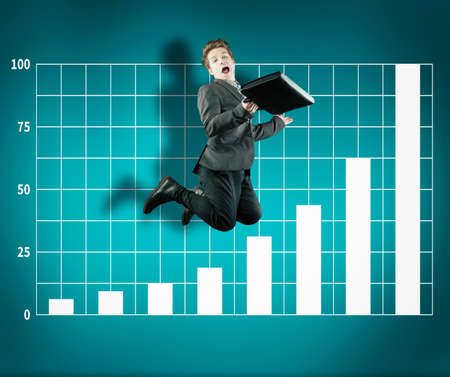 Business man jumping on a simple background with a graph painted on it. The concept of progress. Stock Photo