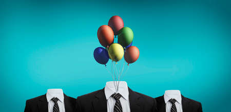 Three business suits without head on a blue background . Business suit with colorful balloons in place of the head .The concept of positive and calm mind. Corporate party celebration. Stock Photo