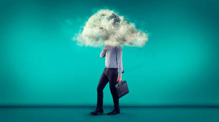 Businessman walking on a blue background with a his head in a cloud.