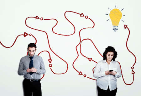 Two people using smartphones against a white wall drawn with the path to success.