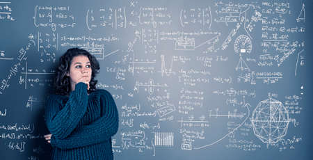 Young woman solving math problema drawn on wall.