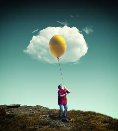 Young man raising up a yellow balloon to a cloud, looking like a fried egg. Stock Photo