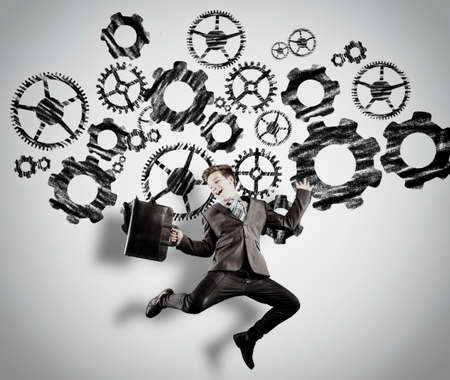 Businessman jumping in front of a white wall patined with engine gear wheels. The concept of hard work pays off.