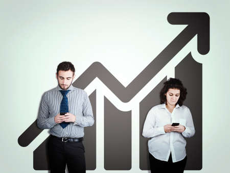 Two people using smartphones against a white wall drawn with a graphic.