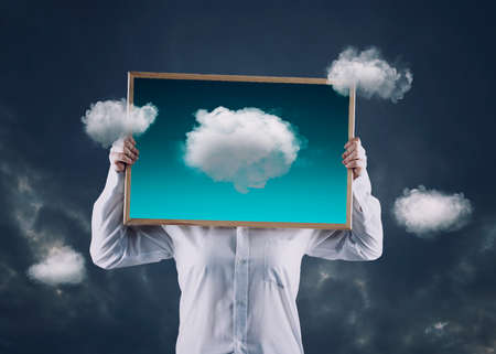 Artist holding an picture with clouds flying away from the frame , on a dramatic sky in background. The concept of fulfilling desires and dreams.