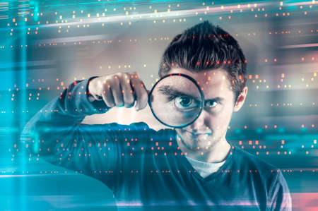 Man looking through magnifying glass to a futuristic interface.