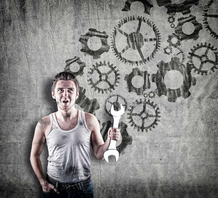 Excited mechanic in standing in front of a wall drawn with engine gear wheels. Stock Photo