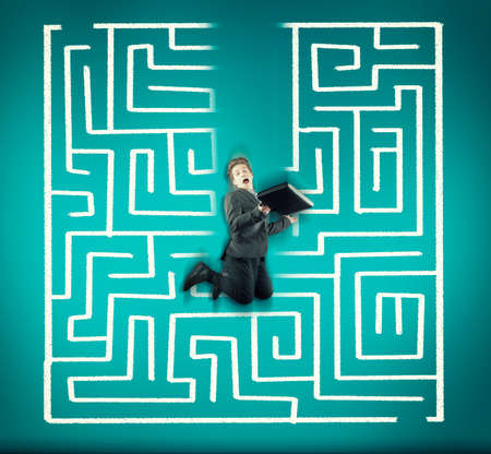 Businessman jumping in front of a maze, earasing the maze. Stock Photo