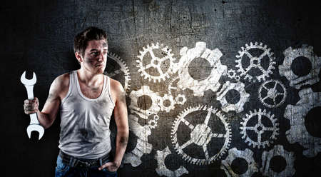 Confused mechanic holding a wrench in front of a blackboard, drawn with a engine wheels gear. Stock Photo